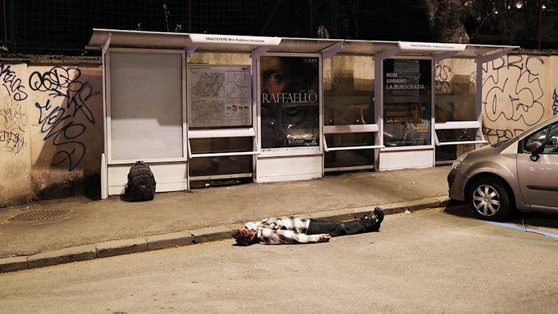 A man wearing a protective mask is on the ground unconscious near a bus stop before being helped by medical personnel as the spread of the coronavirus persists in Italy. Source: Getty Images