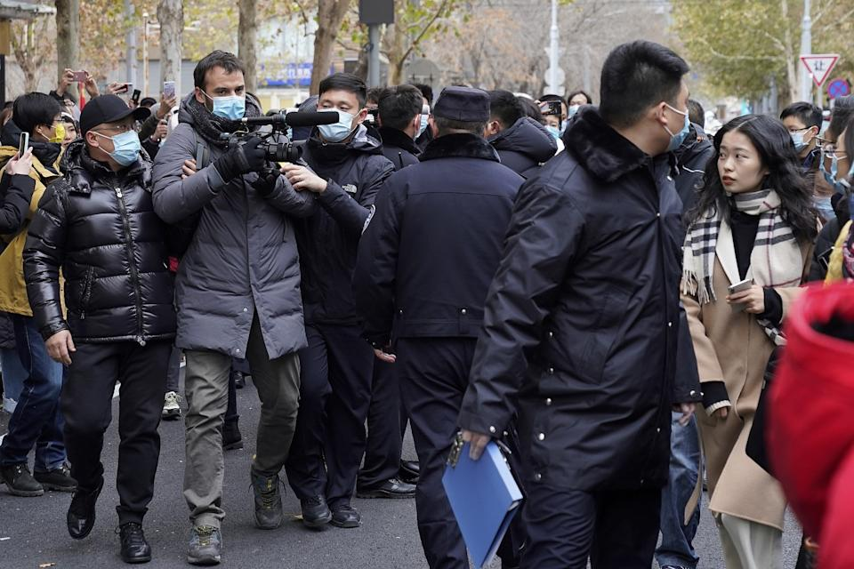 Zhou Xiaoxuan, right, looks as Chinese police block a foreign journalist as she arrives at a courthouse in Beijing.