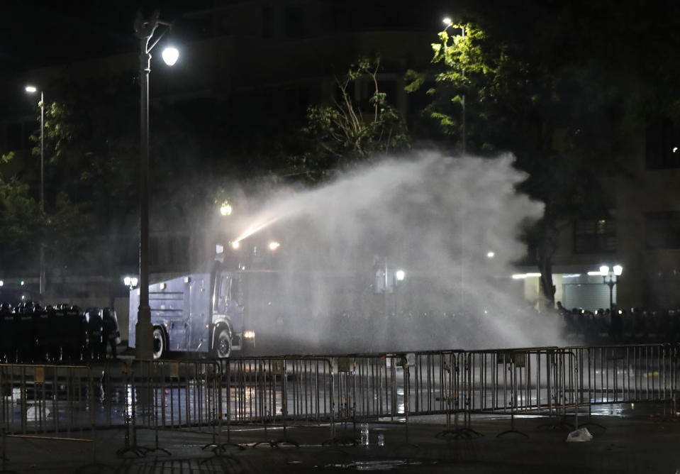 Police use water cannons to disperse protesters Saturday, March 20, 2021 in Bangkok, Thailand. Thailand's student-led pro-democracy movement is holding a rally in the Thai capital, seeking to press demands that include freedom for their leaders, who are being held without bail on charges of defaming the monarchy. (AP Photo/Sakchai Lalit)