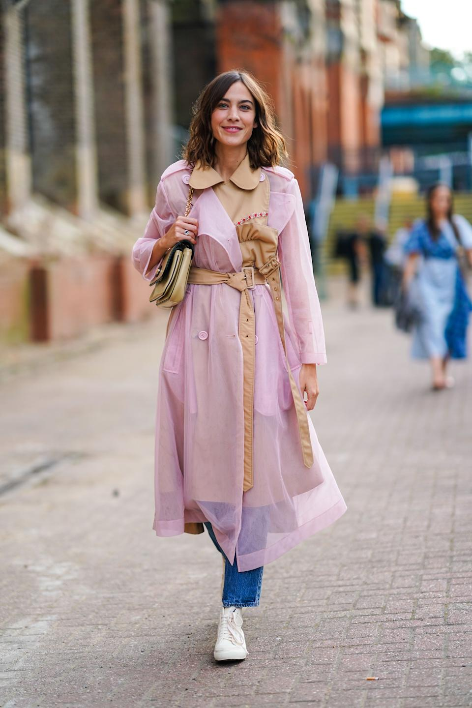 Alexa Chung is seen wearing a pale pink mesh trench coat and jeans. [Photo: Getty Images]