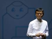 FILE PHOTO: FILE PHOTO - Jack Ma, founder and executive chairman of China's Alibaba Group, speaks in front of a picture of SoftBank's human-like robot named 'pepper' during a news conference in Chiba