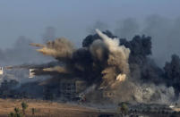 An explosion during an Israeli strike in the northern Gaza Strip is pictured from the Israeli border with Gaza, early morning July 26, 2014, before a cease-fire takes effect. REUTERS/Ronen Zvulun