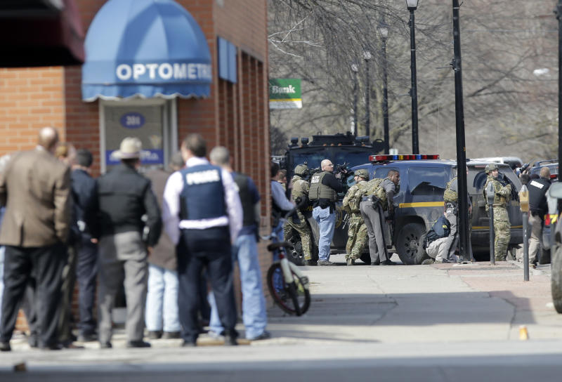 Law enforcement officers take cover along Main Street when shots were fired while searching for a suspect in two shootings that killed four and injured at least two on Wednesday, March 13, 2013, in Herkimer, N.Y. Authorities were looking for 64-year-old Kurt Meyers, said Herkimer Police Chief Joseph Malone. Officials say guns and ammunition were found inside his Mohawk apartment after emergency crews were sent to a fire there Wednesday morning. (AP Photo/Mike Groll)