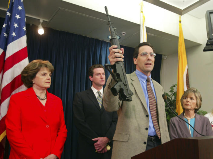 """FILE - In this June 29, 2004, file photo, Steve Sposato, who lost his wife in a shooting, holds an automatic rifle as Sen. Dianne Feinstein, D-Calif., left, then San Francisco Mayor Gavin Newsom, second left, and Sen. Barbara Boxer, D-Calif., right, look on at a news conference in San Francisco. Sposato's wife, Jody Sposato, was killed in 1993 in the high-rise shooting at a San Francisco law firm. U.S. District Judge Roger Benitez of San Diego ruled Friday, June 4, 2021, that the state's definition of illegal military-style rifles unlawfully deprives law-abiding Californians of weapons commonly allowed in most other states and by the U.S. Supreme Court. Gov. Newsom condemned the decision, calling it """"a direct threat to public safety and the lives of innocent Californians, period."""" (AP Photo/Eric Risberg, File)"""