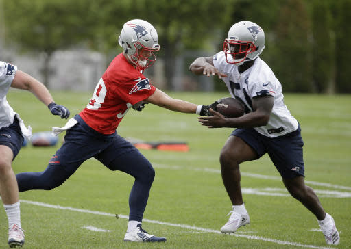 New England Patriots rookie quarterback Danny Etling, left, hands off the ball to rookie running back Sony Michel, right, during NFL football organized team activities practice at the team's training camp, in Foxborough, Mass., Tuesday, May 22, 2018. (AP Photo/Steven Senne)