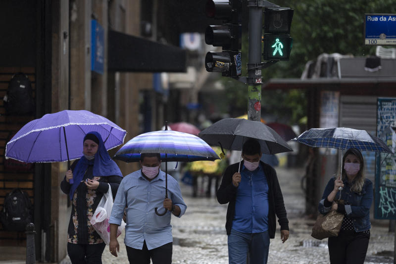 Pedestrians, some wearing protective face masks, cross a street amid the new coronavirus pandemic in downtown, Rio de Janeiro, Brazil, Thursday, July 30, 2020. (AP Photo/Leo Correa)