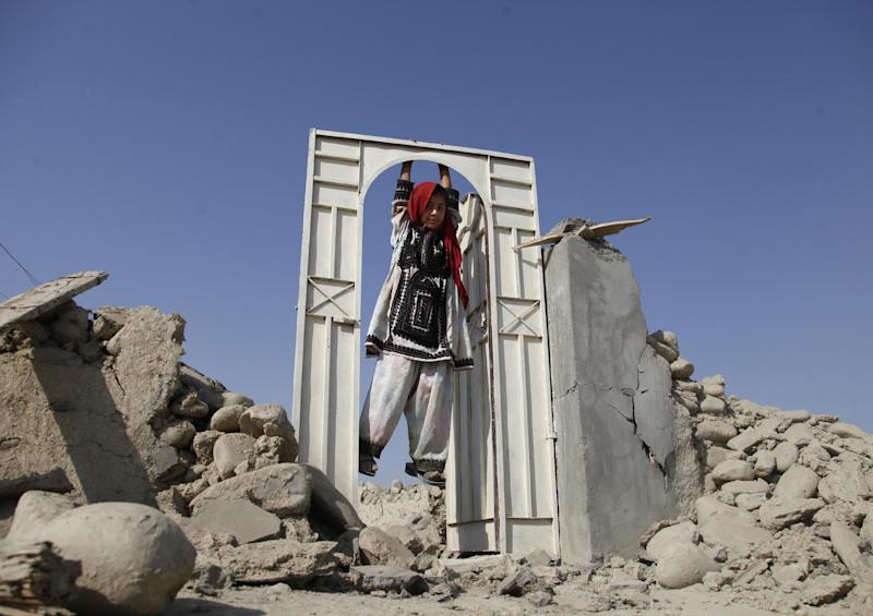 A Pakistani girl plays on the doorway of a house which was destroyed in Tuesday's earthquake, in the remote district of Awaran in Baluchistan province, Pakistan, Friday, Sept. 27, 2013. Desperate Pakistani villagers in remote areas hit by the massive earthquake this week said they are still waiting for government aid to reach them. (AP Photo/Shakil Adil)
