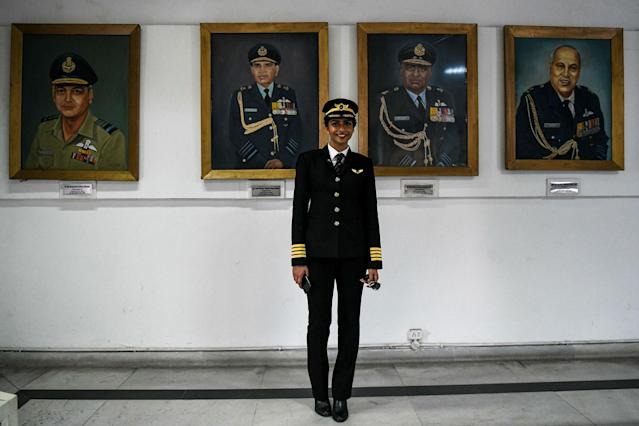 <p>Anny Divya, 31, an Indian pilot who became the youngest woman in the world to captain a Boeing 777 aircraft, poses next to portraits of various air marshals at the Indian Air Force Museum in New Delhi on February 24, 2018. (Photo: Chandan Khanna/AFP/Getty Images) </p>