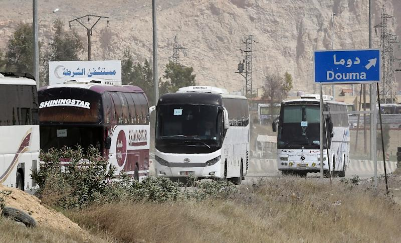 Buses wait at the entrance of Harasta in Eastern Ghouta, on the outskirts of Damascus, on March 22, 2018, after a deal was struck with rebels in the area to evacuate the town (AFP Photo/LOUAI BESHARA)