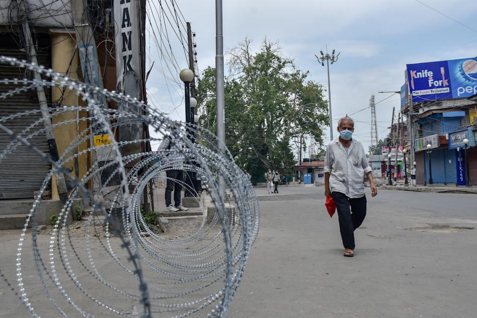 A man wearing a protective face mask walks past a concertina barricade erected by the government forces during a lockdown re-imposed to prevent the spread of coronavirus.Lockdown was re-imposed in Kashmir valley after a sudden surge in COVID-19 cases over the past one week, officials said Strict restrictions have been imposed and no movement of people, except for essential services and medical emergencies, are being allowed. (Photo by Saqib Majeed/SOPA Images/LightRocket via Getty Images)