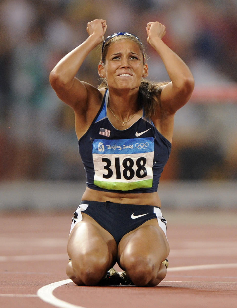 """FILE - In this Aug. 19, 2008, file photo, United States' LoLo Jones reacts after the women's 100-meter hurdles final during the athletics competitions in the National Stadium at the Beijing Olympics in Beijing. When Lolo Jones opens her book, """"Over It,"""" she doesn't start with her biggest accomplishment. Instead, she opens with the """"most painful race"""" of her career—the 100-meter hurdles at the 2008 Beijing Olympics.(AP Photo/Mark J. Terrill, File)"""