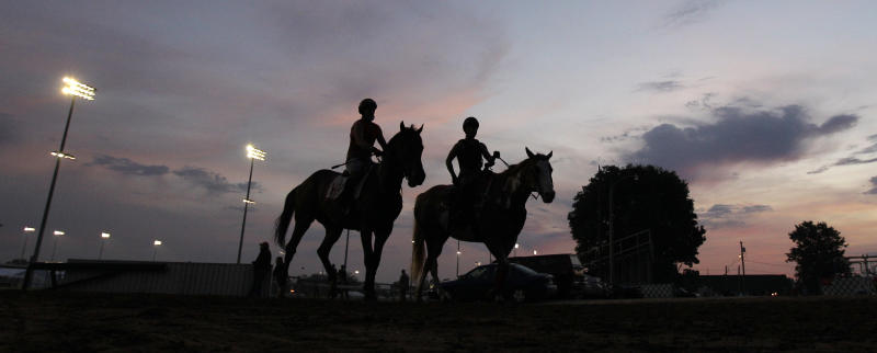 Riders are silhouetted against the dawn sky after a morning workout at Churchill Downs in Louisville, Ky., Monday, April 30, 2012.  The Kentucky Derby horse race is scheduled for Saturday, May 5. (AP Photo/Charlie Riedel)