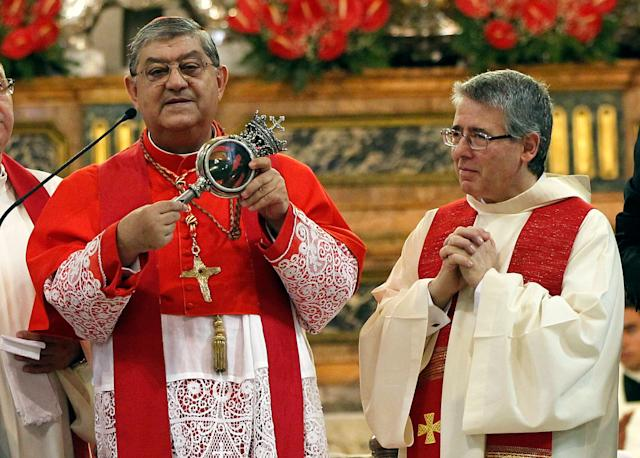 Archbishop of Naples, Cardinal Crescenzio Sepe (L) holds a flask believed to contain drops of liquefied blood of San Gennaro in Naples Cathedral, Italy, in this September 19, 2013 file photo.