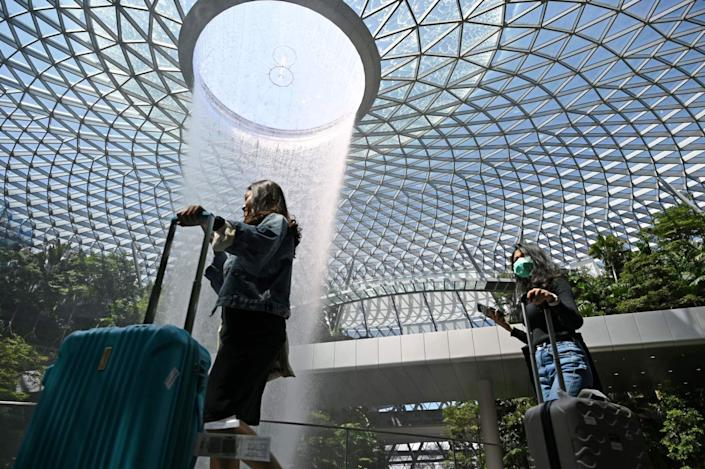 """An indoor waterfall at Changi Airport. Officials are touting health and safety features over amenities to lure back travelers. <span class=""""copyright"""">(AFP/Getty Images)</span>"""