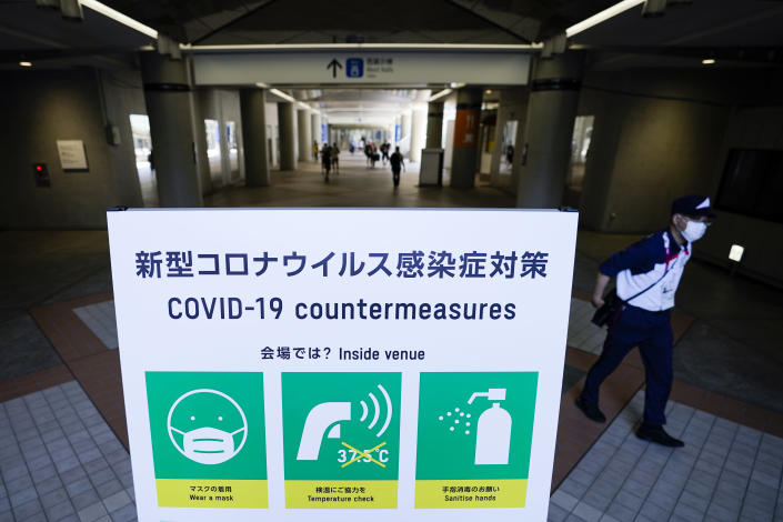 FILE - In this July 22, 2021, file photo, security officer passes a sign displaying COVID-19 protocols in the Main Press Center at the 2020 Summer Olympics, in Tokyo, Japan. (AP Photo/John Minchillo, File)