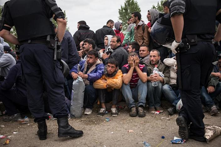 Croatian police officers stand by as people wait to enter the Opatovac transit center for migrants and refugees on September 22, 2015 (AFP Photo/Federico Scoppa)