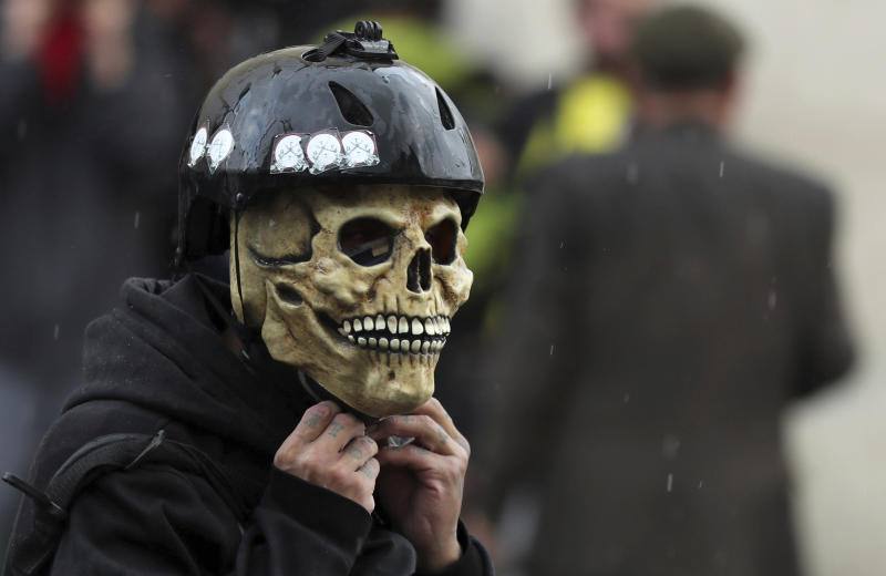 An anti-government demonstrators wears a skull mask and a helmet during a nationwide strike, at Bolivar square in downtown Bogota, Colombia, Thursday, Nov. 21, 2019. Colombia's main union groups and student activists called for a strike to protest the economic policies of Colombian President Ivan Duque government and a long list of grievances. (AP Photo/Fernando Vergara)