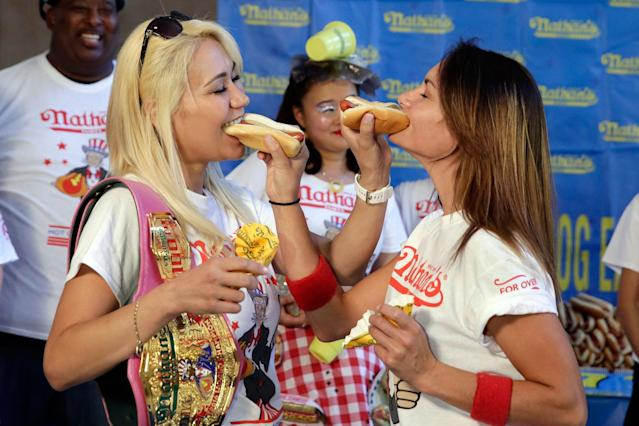 <p>Current women's champion Miki Sudo, left, of Las Vegas, and challenger Michelle Lesco, of Tuscon, Ariz., feed each other a hot dog Monday, July 3, 2017, during the weigh-in for the 2017 Nathan's Hot Dog Eating Contest, in Brooklyn Borough Hall, in New York. Ms. Suto weighed-in at 126 pounds, while Ms. Lesco tipped the scales at 104.5 pounds.(AP Photo/Richard Drew) </p>