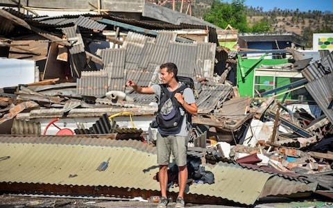 A foreign tourists stands near damaged buldings as he tries to flag down a car following a strong earthquake in Pemenang, North Lombok - Credit: Reuters