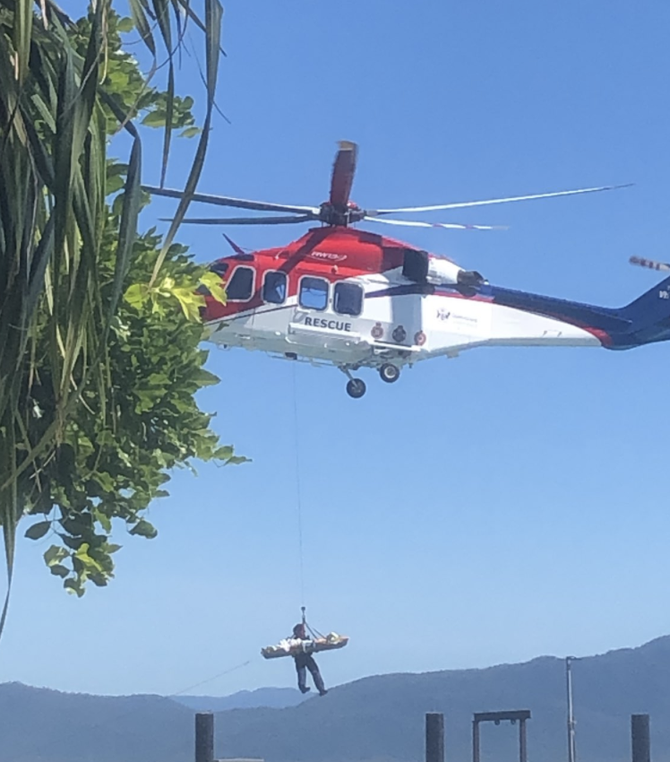 Photo shows woman being winched up into a helicopter after being attacked by a shark in Queensland.