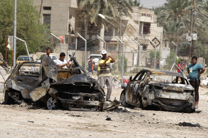 Civilians inspect the aftermath of a car bomb attack in Baghdad, Iraq, Thursday, Aug. 15, 2013. A wave of car bombs in the Iraqi capital on Wednesday killed 26 people and wounded dozens, the latest attacks in a months-long surge in violence. More than 3,000 people have been killed in violence during the past few months, raising fears Iraq could see a new round of widespread sectarian bloodshed similar to that which brought the country to the edge of civil war in 2006 and 2007. (AP Photo/Karim Kadim)