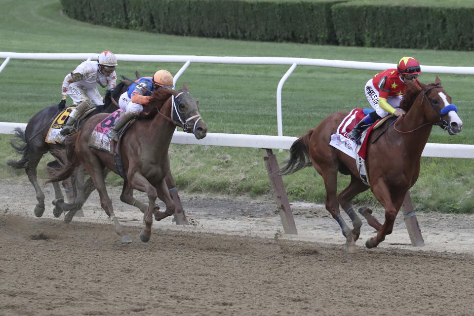 Justify, right, ridden by Mike Smith, leads the field around the far turn during the Belmont Stakes horse race, Saturday, June 9, 2018, at Belmont Park in Elmont, N.Y. Justify won the race, to claim horse racing's Triple Crown (AP Photo/Mary Altaffer)