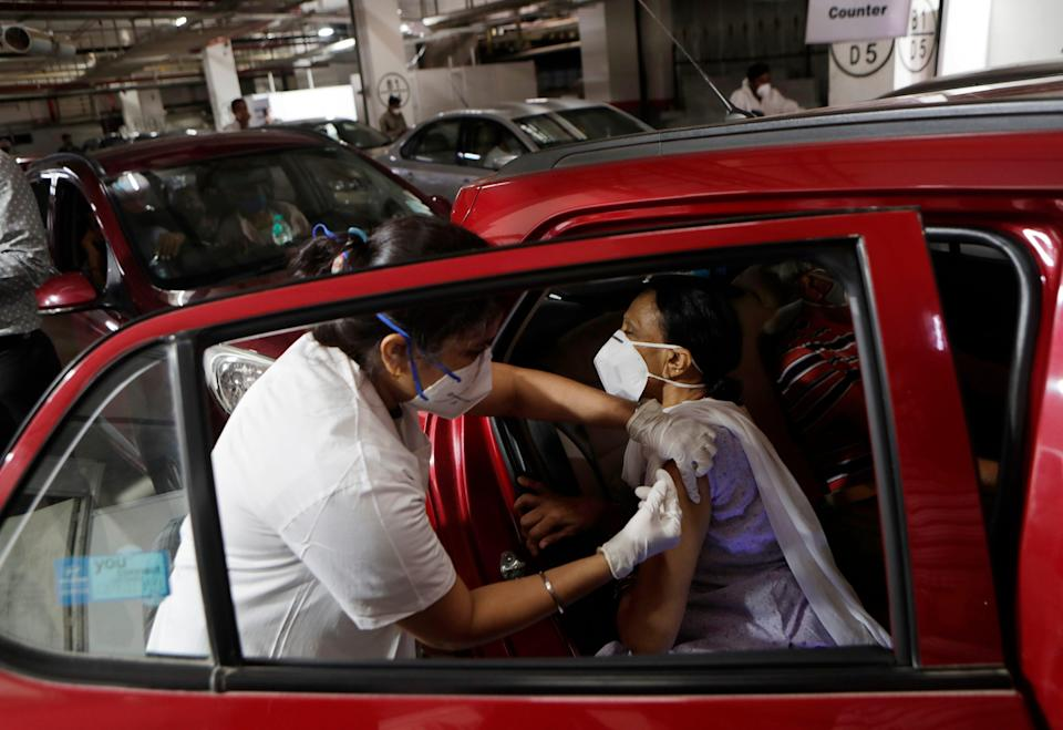 A woman receives a vaccine for COVID-19 in her car at a drive-in vaccination centre in Mumbai, India, May 4, 2021. COVID-19 infections and deaths are mounting with alarming speed in India with no end in sight to the crisis.