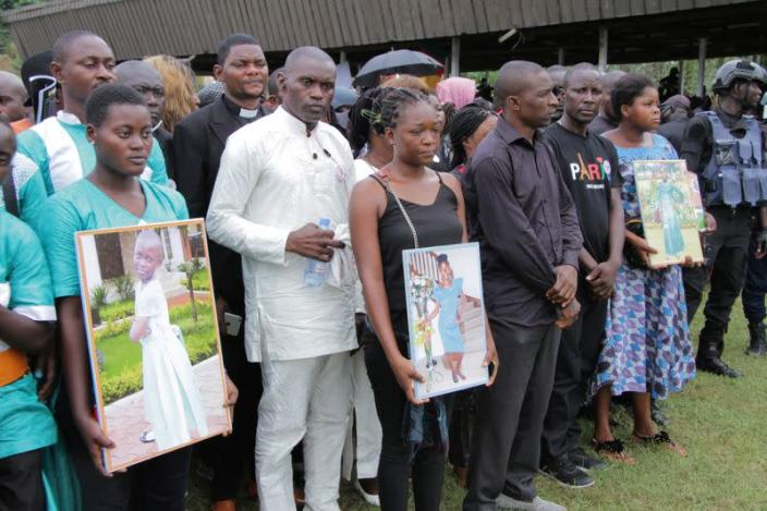 FILE PHOTO: Family members line up at a mass funeral of seven children who were killed by unidentified assailants in a classroom of a secondary school in Kumba