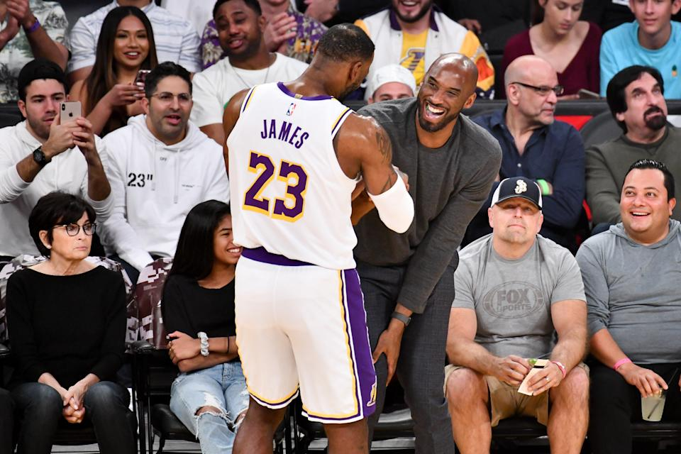 Kobe Bryant embraces LeBron James during a basketball game between the Los Angeles Lakers and the Atlanta Hawks at Staples Center on November 17, 2019 in Los Angeles, California. (Photo by Allen Berezovsky/Getty Images)