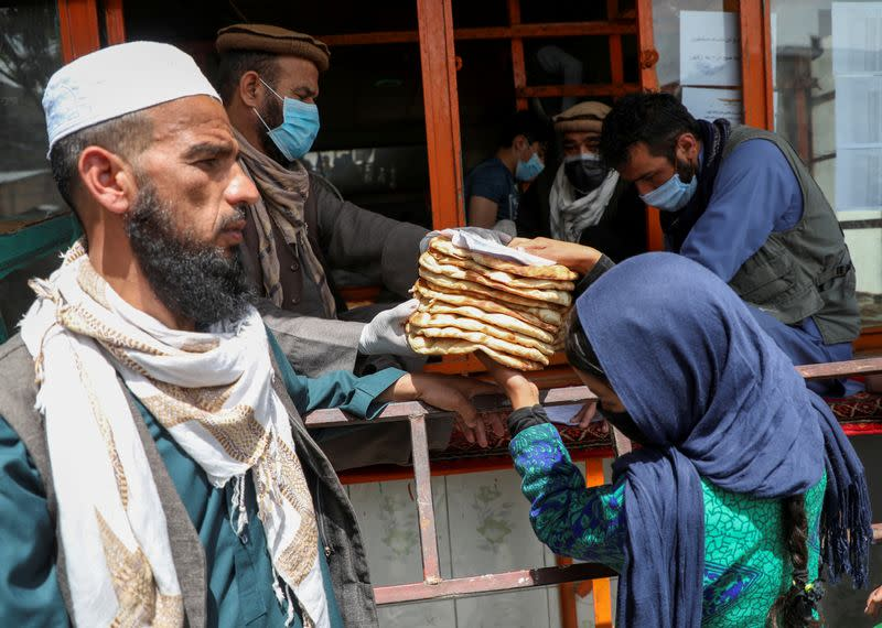 FILE PHOTO: An Afghan girl receives free bread distributed by the government, outside a bakery, during the coronavirus disease (COVID-19) outbreak in Kabul