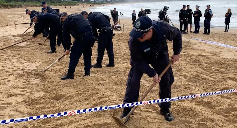 NSW Police officers dig in the sand at Umina Beach after what is believed to be a human jaw bone was found.