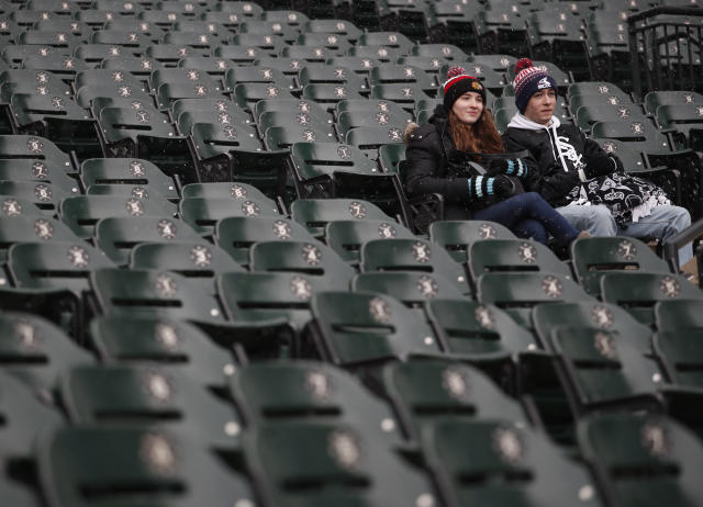 Two fans sit in the stands before a baseball game between the Chicago White Sox and the Tampa Bay Rays in Chicago, Monday, April 9, 2018. (AP Photo/Jeff Haynes)