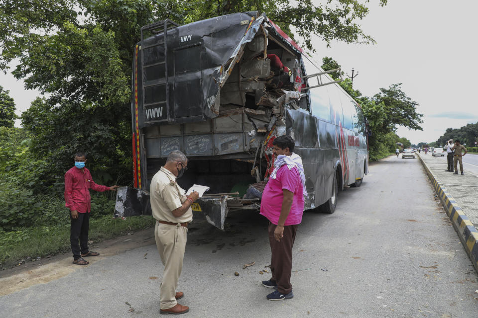 A police officer takes notes next to a parked bus onto which a truck struck overnight in Barabanki, Uttar Pradesh state, India, Wednesday, July 28, 2021. Police say a truck struck a group of laborers sleeping under the parked bus on the side of a highway in northern India, killing more than a dozen of them. (AP Photo/Sumit Kumar)