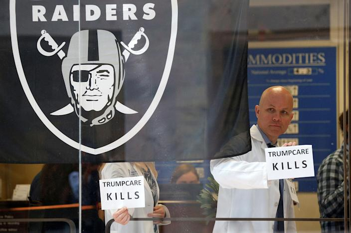 <p>Beside a Raiders football team flag, healthcare activists hold up signs while occupying the office of Senator Dean Heller to protest the Republican healthcare bill at the Capitol in Washington, D.C., July 10, 2017. (Photo: Kevin Lamarque/Reuters) </p>
