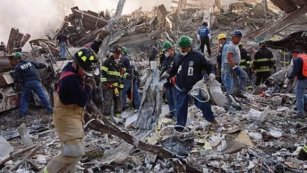In this Sept. 13, 2001, photo, firefighters and emergency personnel in New York remove debris from the site where the World Trade Center towers fell.  (Stephen Chernin/Associated Press - image credit)