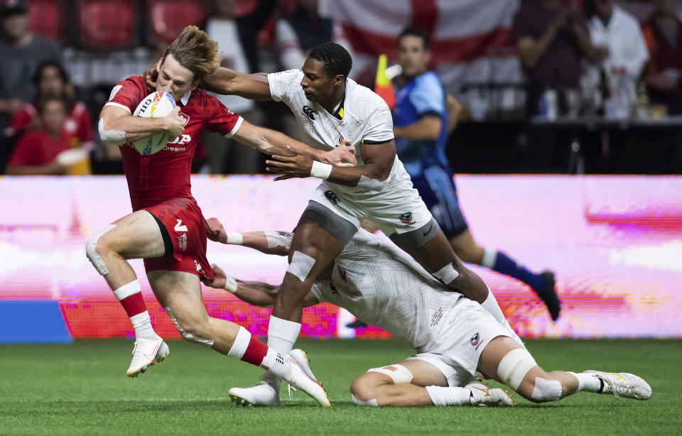 Canada's Brennig Prevost, left, is tackled by United States' David Still, front right, and Joe Schroeder during an HSBC Canada Sevens rugby game in Vancouver, British Columbia, Saturday, Sept. 18, 2021. (Darryl Dyck/The Canadian Press via AP)
