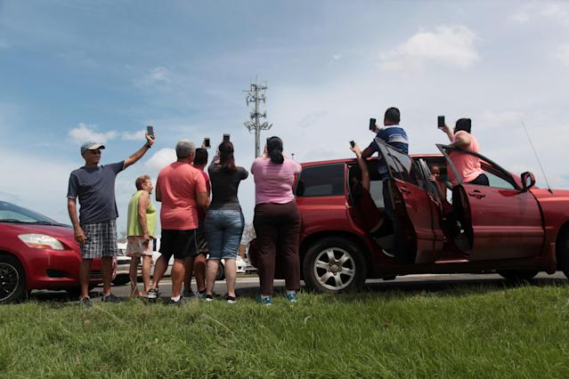 <p>People stop on a highway near a mobile phone antenna tower to check for mobile phone signal, after the area was hit by Hurricane Maria, in Dorado, Puerto Rico, Sept. 22, 2017. (Photo: Alvin Baez/Reuters) </p>