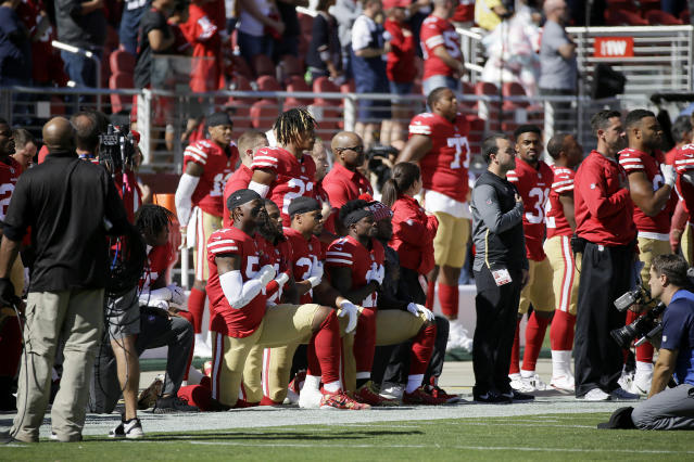 San Francisco 49ers players kneel during the performance of the national anthem on Sunday. (AP)