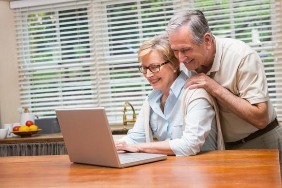 Man and woman in their sixties looking at laptop computer.