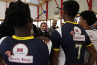 French President Emmanuel Macron, center, and former NBA player Tony Parker, behind, talk with members of a basketball team at a basketball playground in Tremblay-en-France, outside Paris, Thursday, Oct.14, 2021. French President Emmanuel Macron will promote sports ahead of the 2024 Olympic Games in Paris. (AP Photo/Francois Mori, Pool)