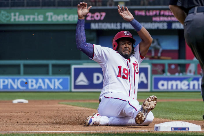Washington Nationals' Josh Bell slides into third base during the third inning of a baseball game against the Colorado Rockies at Nationals Park, Sunday, Sept. 19, 2021, in Washington. (AP Photo/Andrew Harnik)