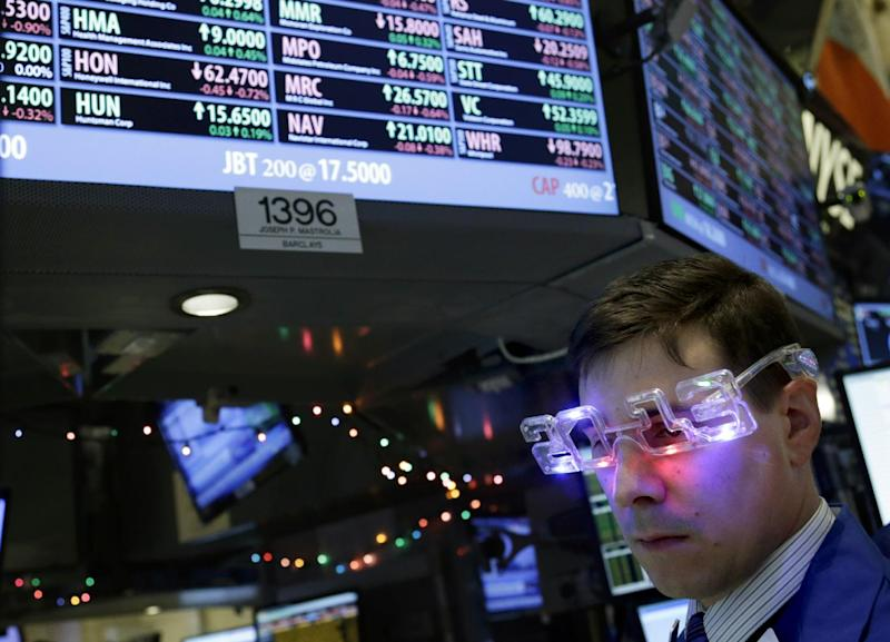 "A trader wearing ""2013"" glasses works on the floor at the New York Stock Exchange in New York, Monday, Dec. 31, 2012.  The stock market struggled for direction Monday morning after five days of losses, with the ""fiscal cliff"" just hours away and lawmakers yet to reach a solution. (AP Photo/Seth Wenig)"