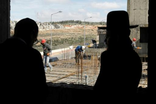 Ultra-orthodox Jews stand in the Israeli settlement of Beitar Illit as Palestinian labourers work at a construction site on February 14, 2018
