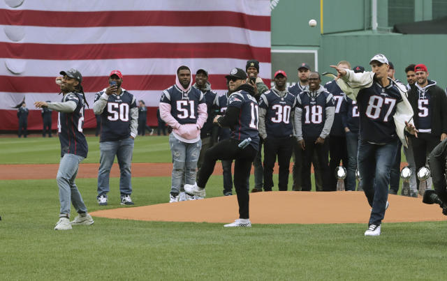 With Super Bowl winning teammates behind them, New England Patriots' Stephon Gilmore, left, Julian Edelman, center, and Rob Gronkowski, right, toss the ceremonial first pitch before the home opener baseball game between the Red Sox and the Toronto Blue Jays, Tuesday, April 9, 2019, in Boston. (AP Photo/Charles Krupa)