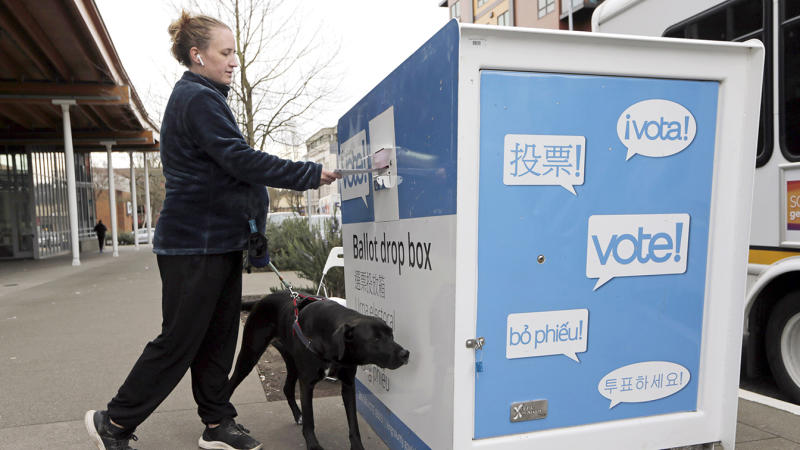 Matilda Jagger with her dog Basil drops off a ballot in the Washington State primary, Tuesday, March 10, 2020 in Seattle. Washington is a vote by mail state. (John Froschauer/AP Photo)