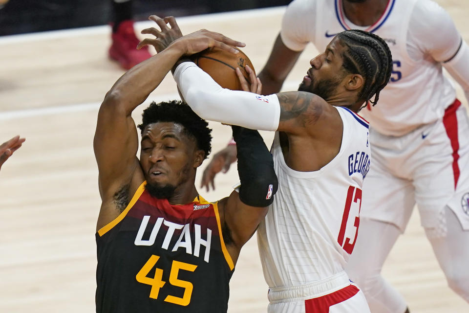 Utah Jazz guard Donovan Mitchell (45) and Los Angeles Clippers guard Paul George (13) vie for the ball during the first half of Game 2 of a second-round NBA basketball playoff series Thursday, June 10, 2021, in Salt Lake City. (AP Photo/Rick Bowmer)