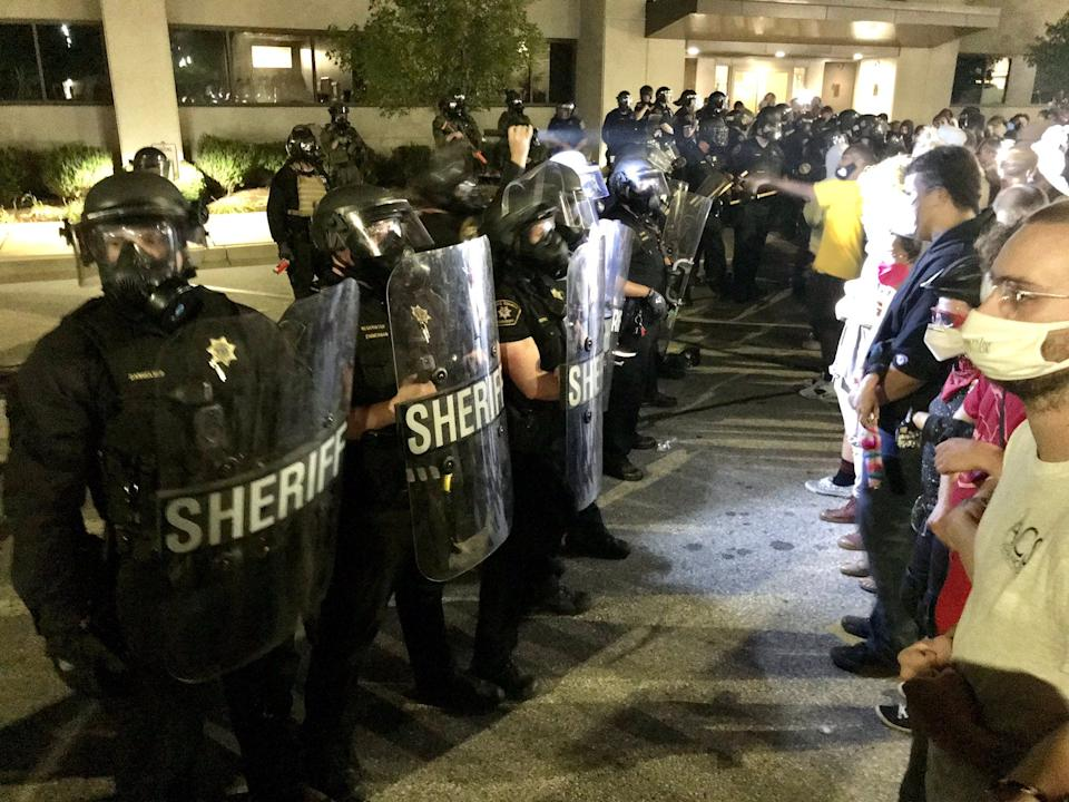 Sheriff deputies in riot gear and protesters face off outside the Kenosha Police Department on Aug. 23, 2020, after an officer shot Jacob Blake.