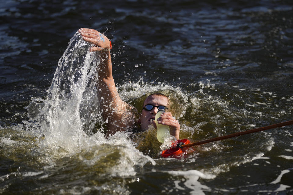 Ferry Weertman, of the Netherlands grabs a bottle at a feeding station during the men's marathon swimming event at the 2020 Summer Olympics, Thursday, Aug. 5, 2021, in Tokyo, Japan. (AP Photo/Jae C. Hong)