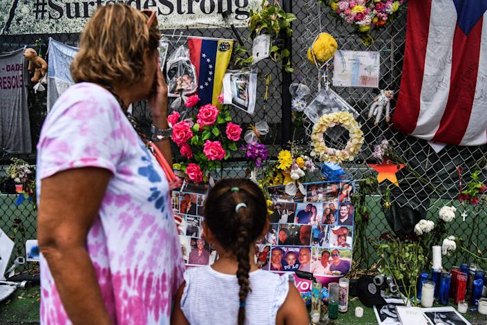 In this file photo taken on July 24, 2021, a woman cries as she visits a makeshift memorial where the partially collapsed Champlain Towers South building stood in Surfside, Florida. (Photo by CHANDAN KHANNA / AFP)