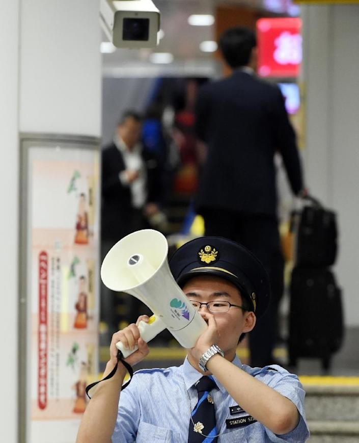 A station attendant makes an announcement about the resumption of shinkansen bullet train services at Tokyo station on June 30, 2015 after service was disrupted due to an apparent suicide attempt on board a moving train (AFP Photo/Toshifumi Kitamura)